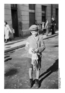 A young Jewish boy sells white armbands in Radom, Poland, 1940